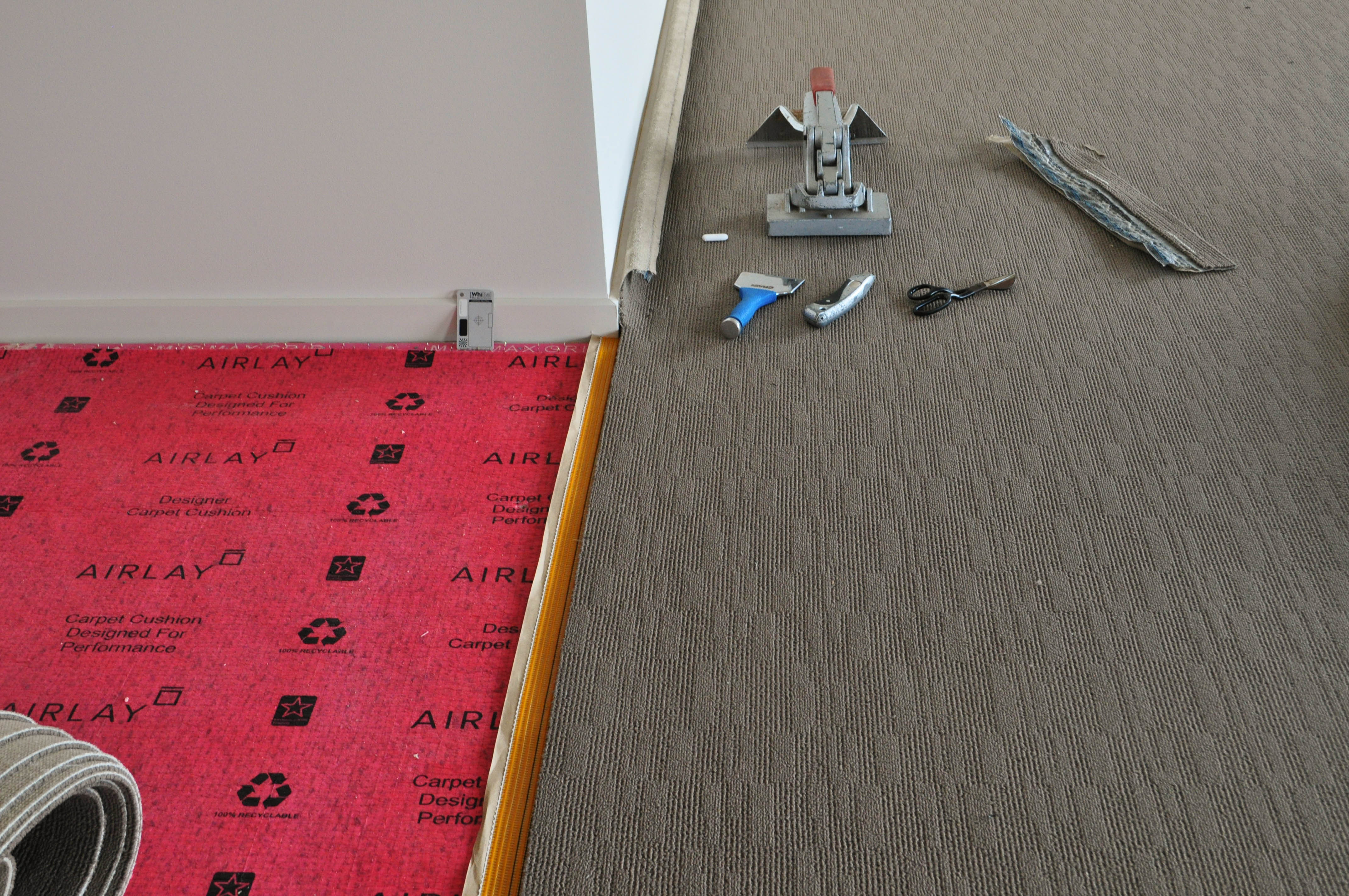 carpet laying process under way by Concord Floors, showing a roll of carpet stretched out and prepared for joining to other carpet roll