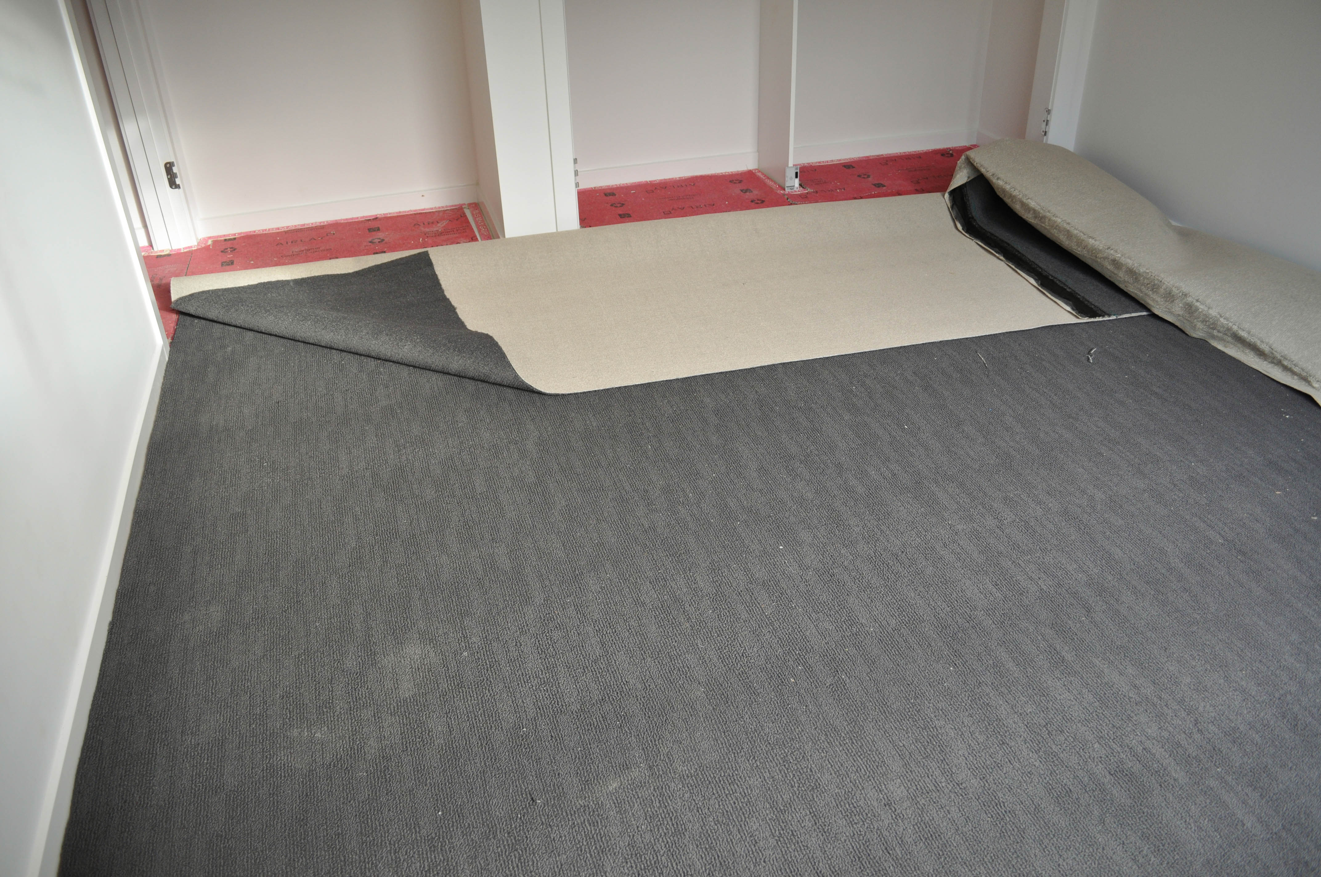 carpet laying process under way by Concord Floors, showing a roll of carpet stretched out, on top of installed red underlay in a home in