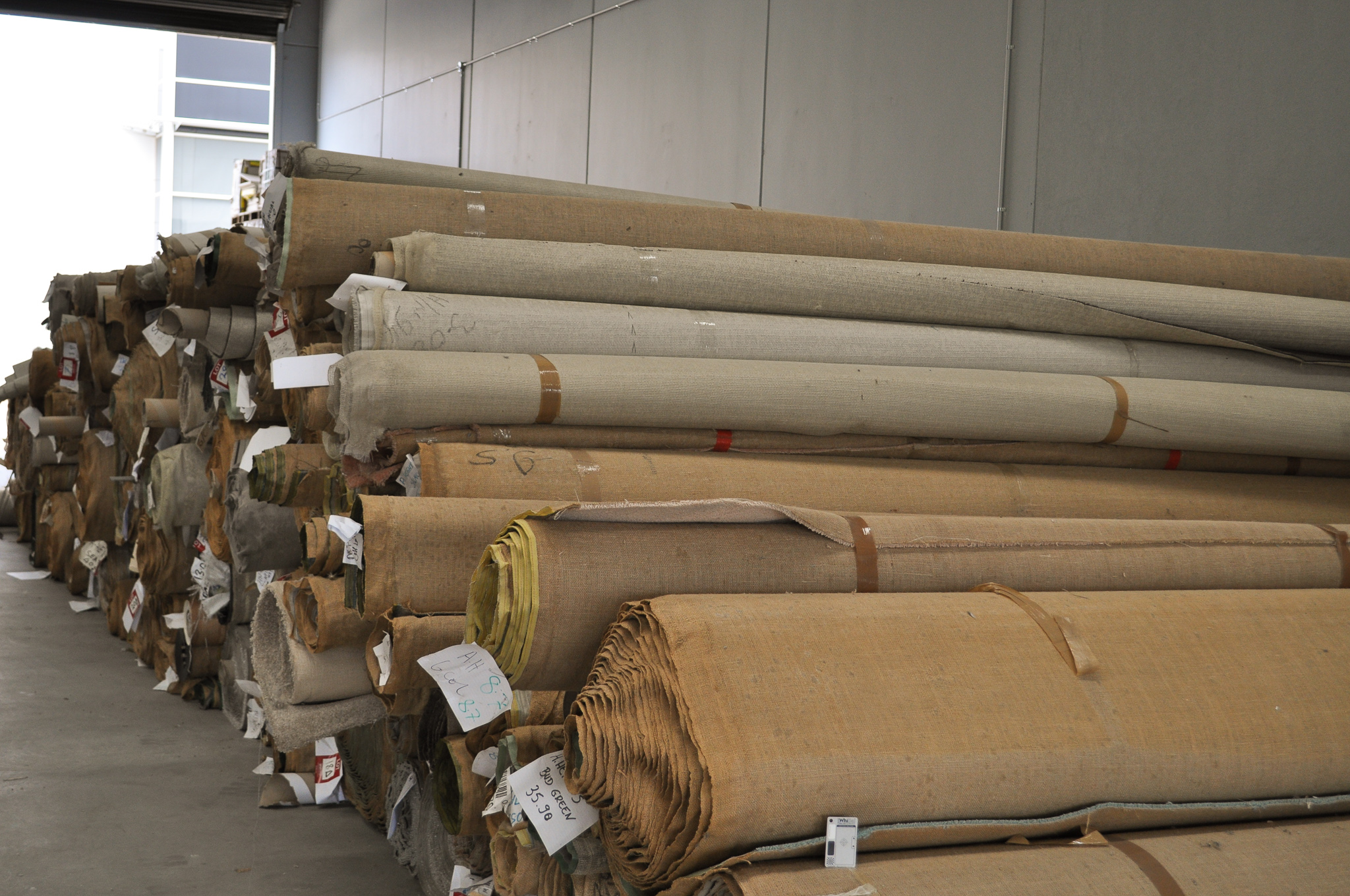 rolls of carpet in the warehouse of Concord Floors, they being carpet stock of Concord Floors.