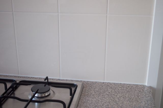 shows a kitchen benchtop and upright wall next to the benchtop where the ceramic wall tile installation process is complete, in Hoppers Crossing,