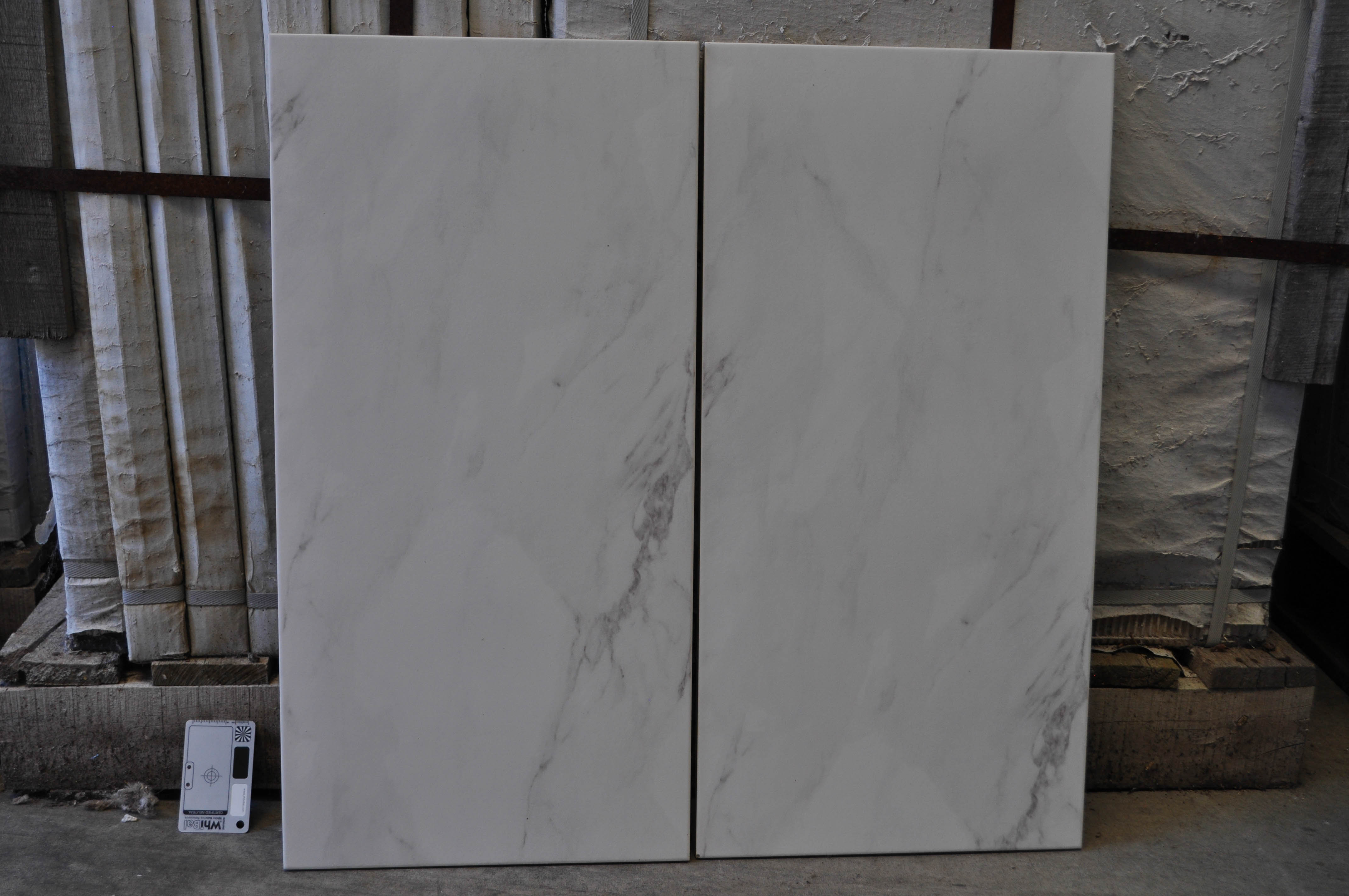 a sales sample of a 30cm x 60cm porcelain tile, with a white marble look, available for purchase from Concord